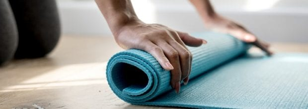 A person rolling up a yoga mat