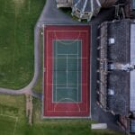 An aerial view of a full size backyard tennis court
